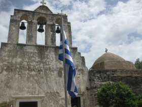 A Greek flag before a classic church in Naxos.